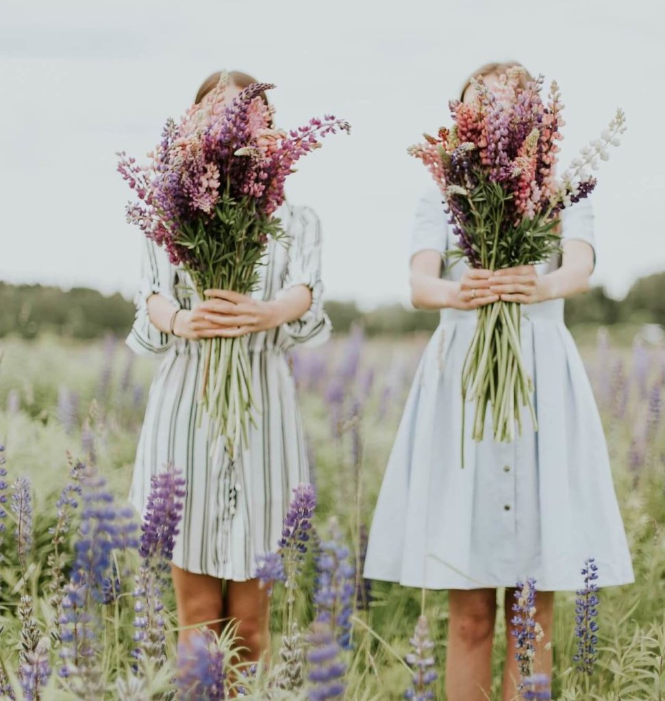 Junge Frauen mit Blumenstrauß auf einer Blumenwiese